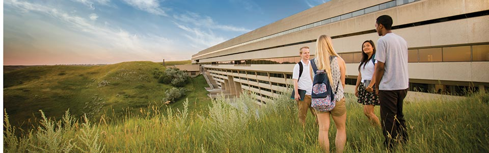 University of Lethbridge campus: students in the long grass on a hill of the university's building