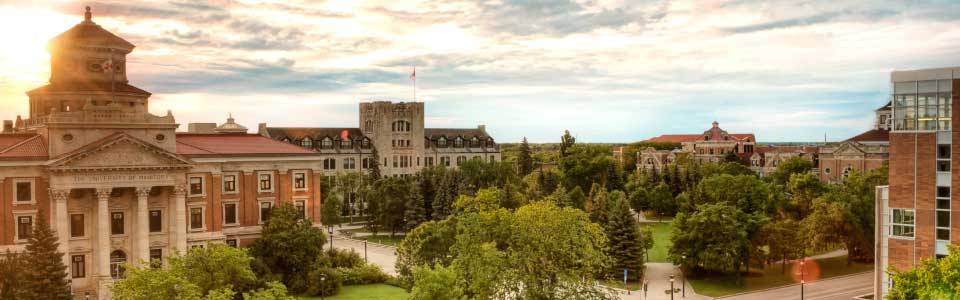University of Manitoba campus: view of historic buildings and trees with sunset.